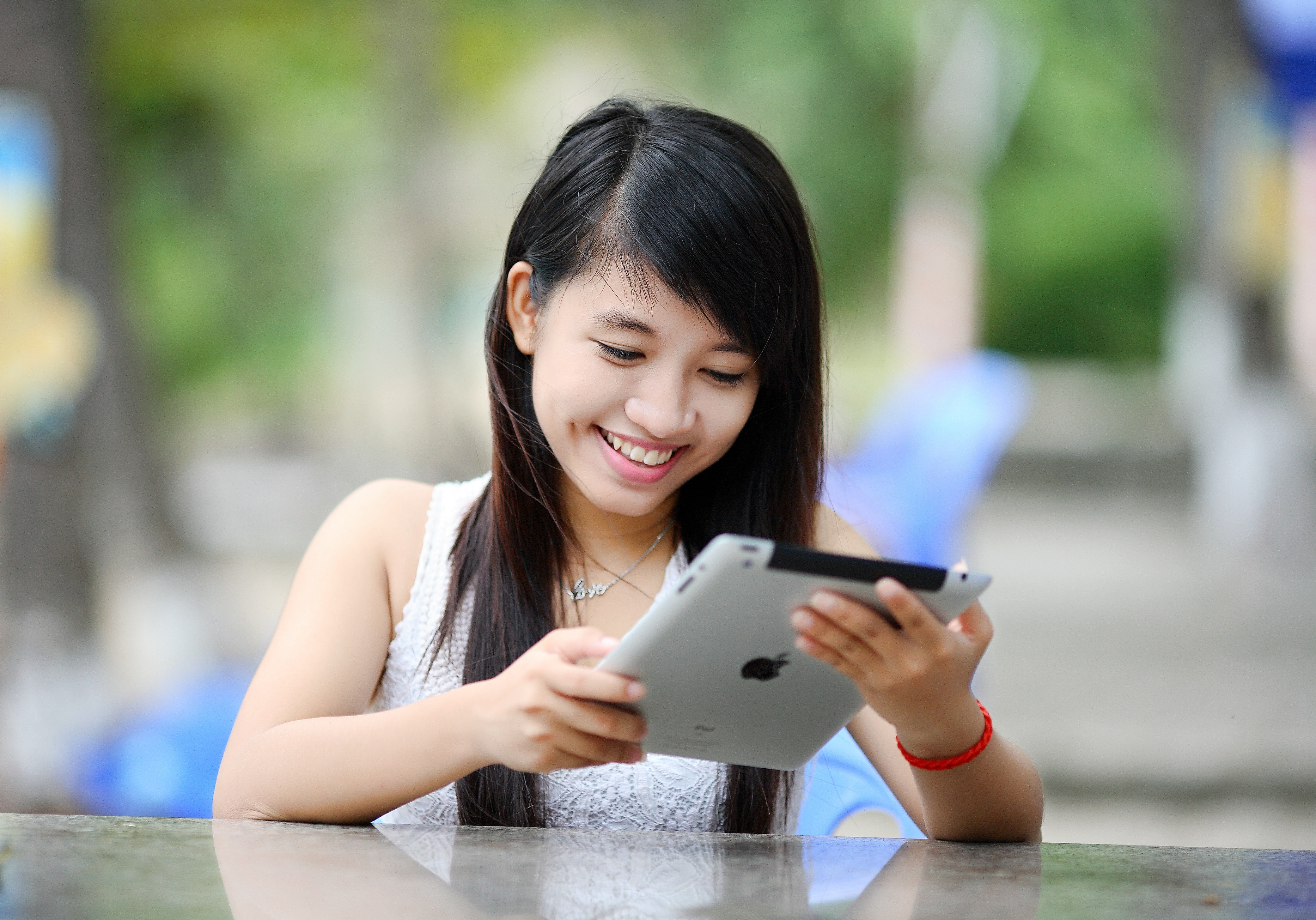 entertainment multimedia computing course by a Asian girl looking at an ipad
