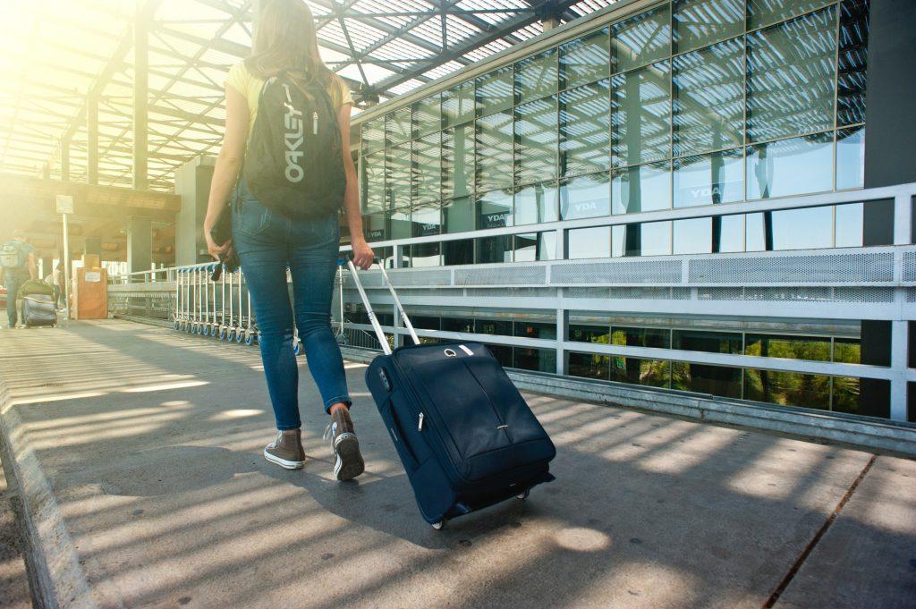 senior high school travel itinerary of a woman pulling a trolley bag