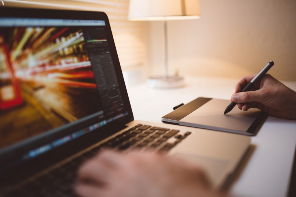 Animator hand using a macbook tablet to draw images