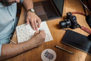 A multimedia course graduate scribbling his creative ideas on his journal