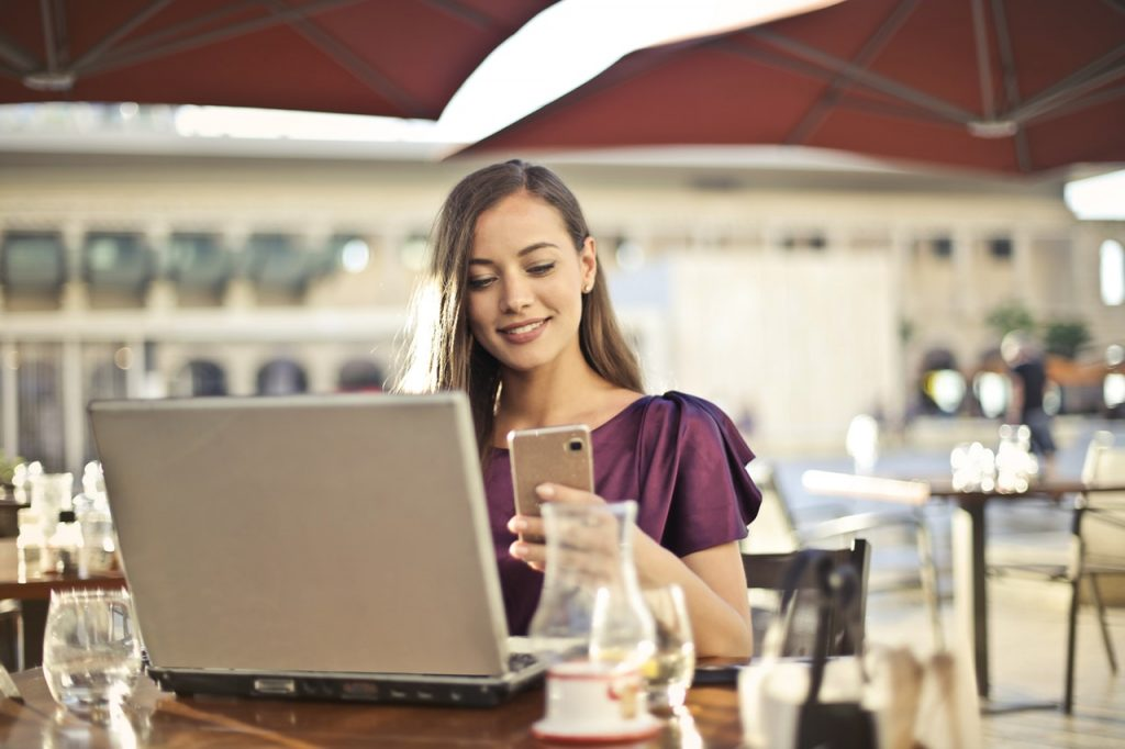 Woman using mobile phone and laptop - apps for millennials