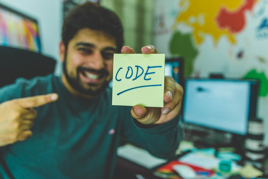 Smiling man holding a sticky note who is happy with Python programming