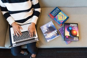 Entertainment and multimedia computing student with MacBook and books